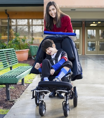 A happy Support Worker pushes a child in his wheelchair.